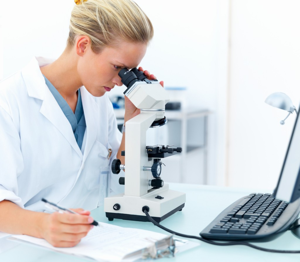 Young female researcher looking into a microscope and writing notes at laboratory